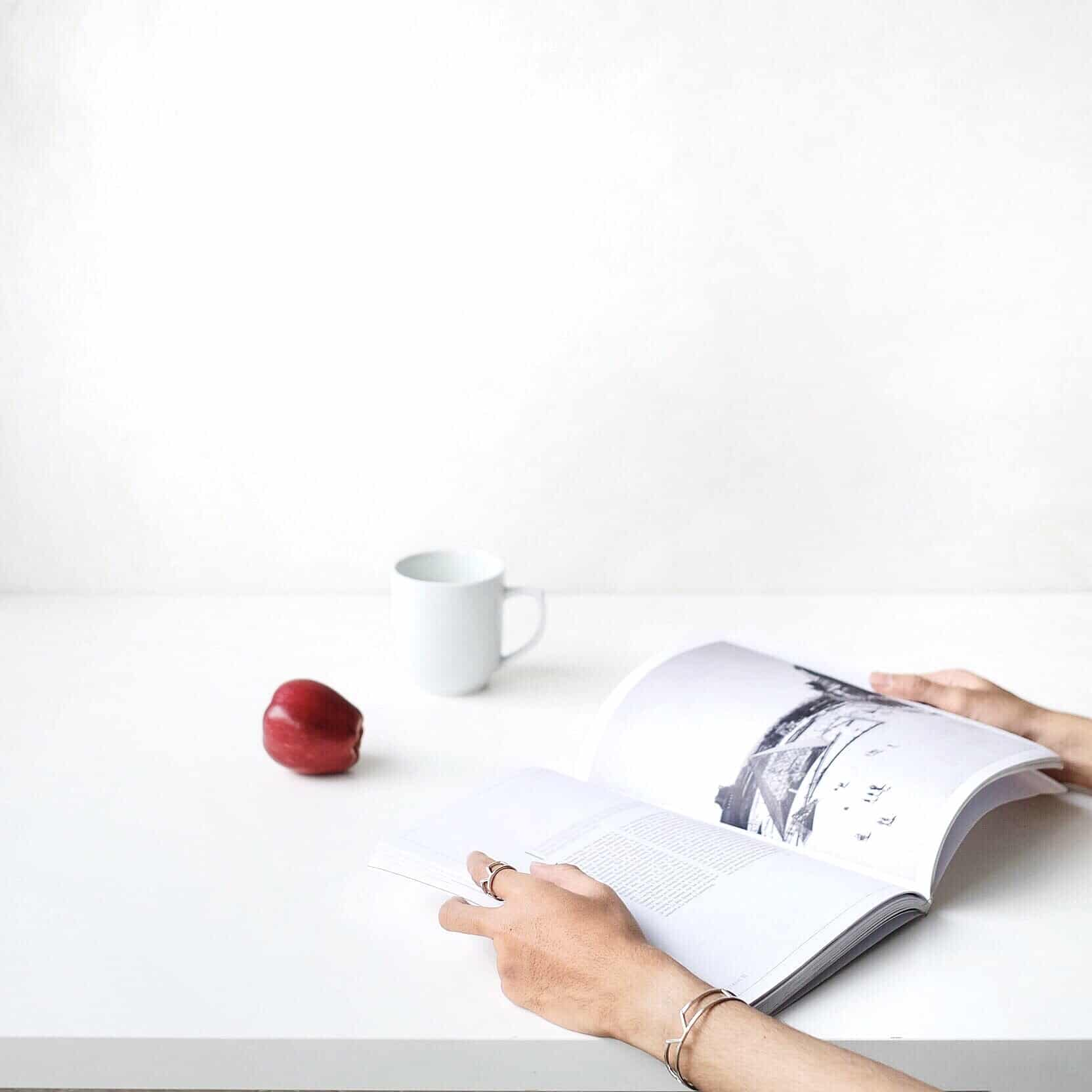 Woman's hands next to an apple while reading book