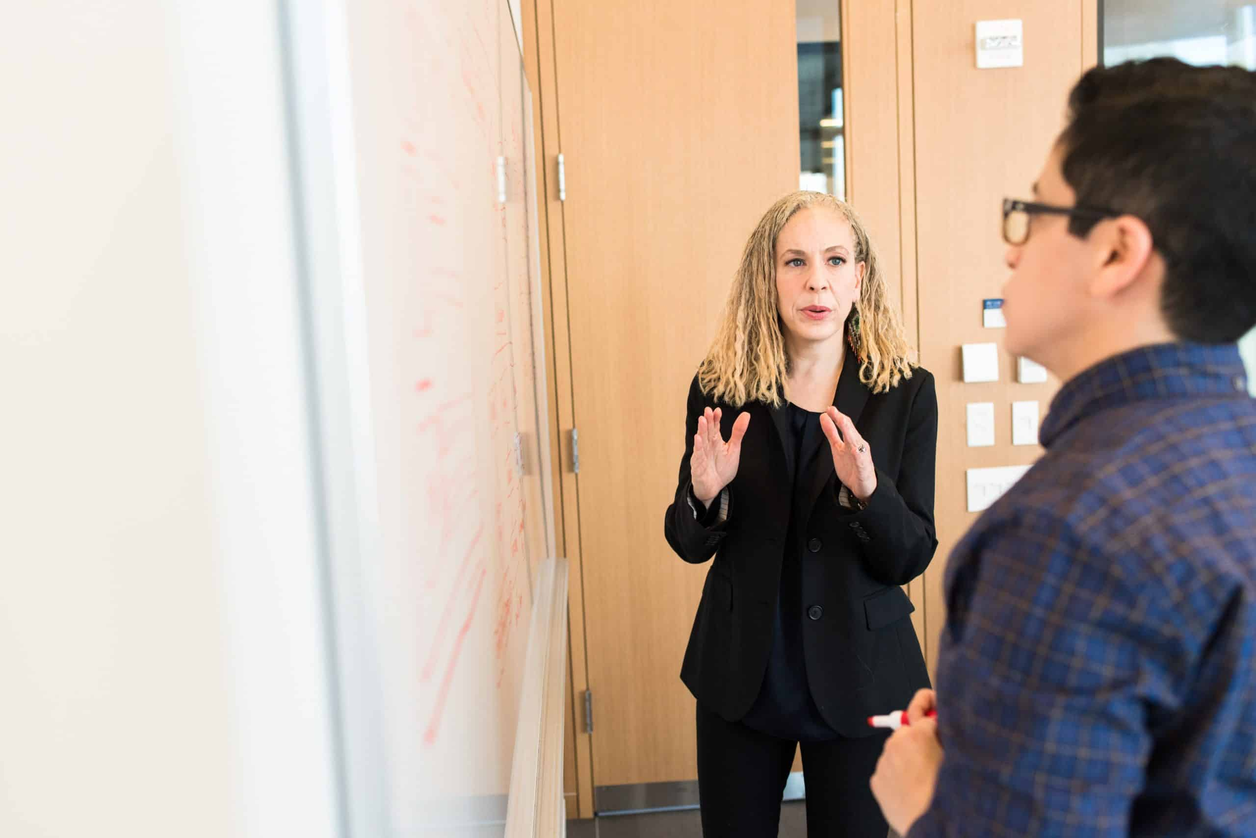 Woman speaking to coworker in front of a white board