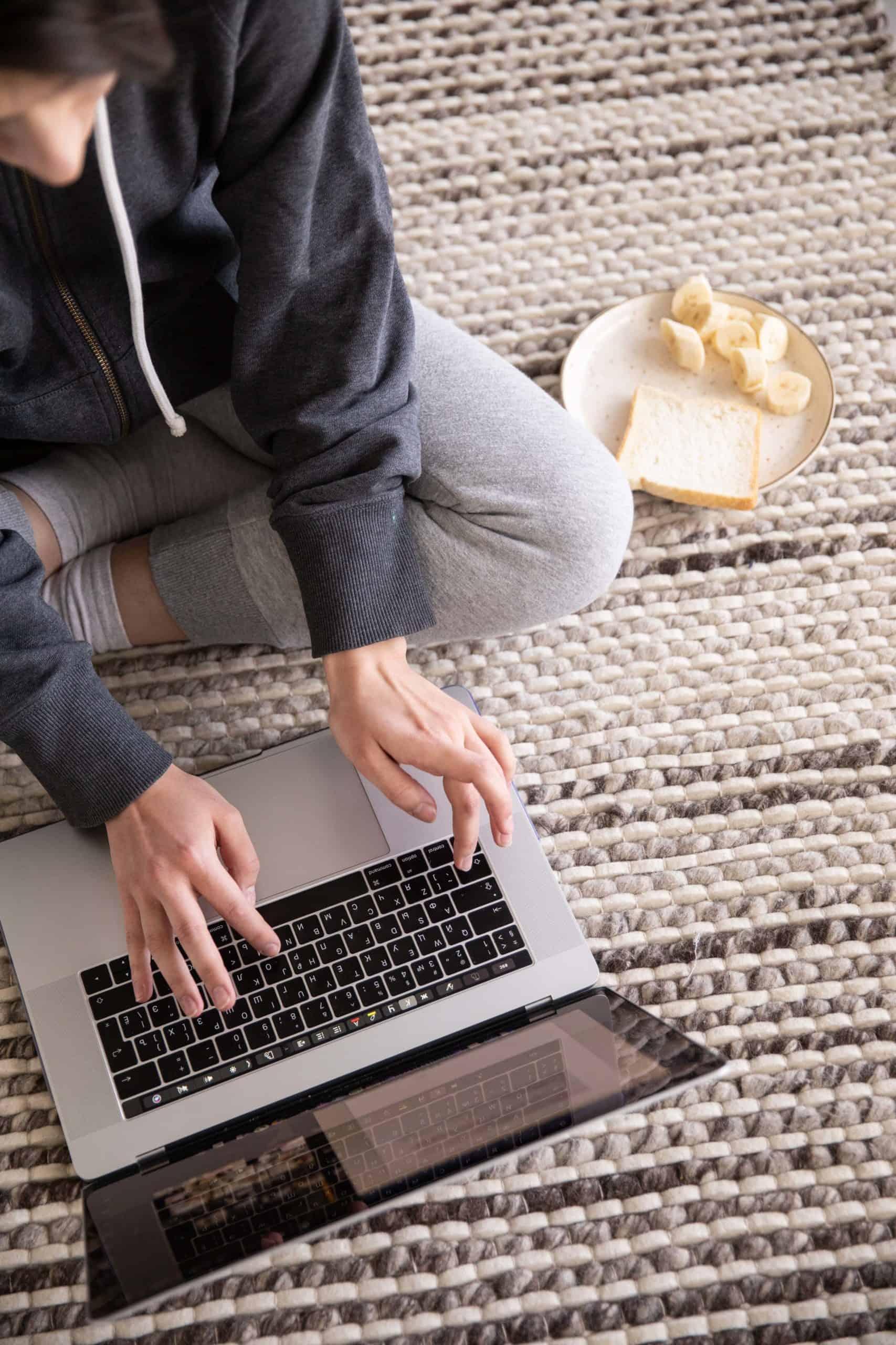 Woman working on laptop on floor