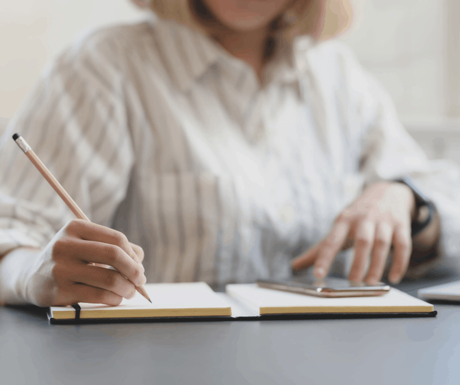 Woman writing and looking at cell phone